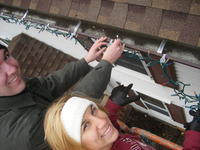 Mike & Heather putting lights on the gutters.